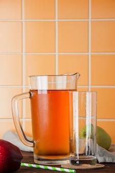 Succo di mele freddo in una tabella su una priorità bassa arancione delle mattonelle. vista laterale. spazio per il testo
