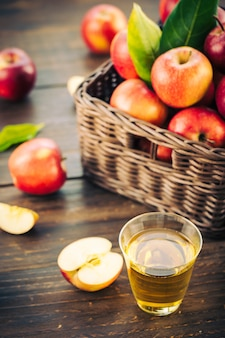 Succo di mele in vetro con mela nel cestino