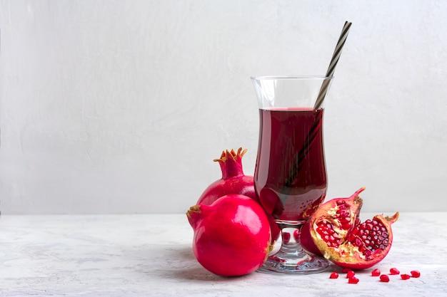 Succo di melograno rosso in un bicchiere su sfondo grigio