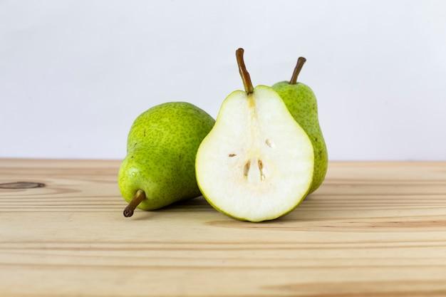 Succo di pera, con i frutti accanto ad esso su uno sfondo bianco. frutta pera