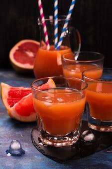 Succo di pomelo fresco con ghiaccio sopra fondo di legno scuro