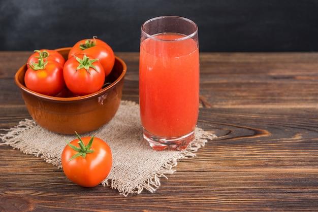 Succo di pomodoro con pomodori su fondo nero e in legno.