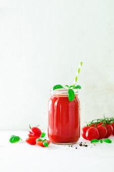 Succo di pomodoro fresco biologico in un vaso di vetro, basilico, ciliegia, sale, pepe e paglia sulla luce. pulire il mangiare e il concetto di dieta.