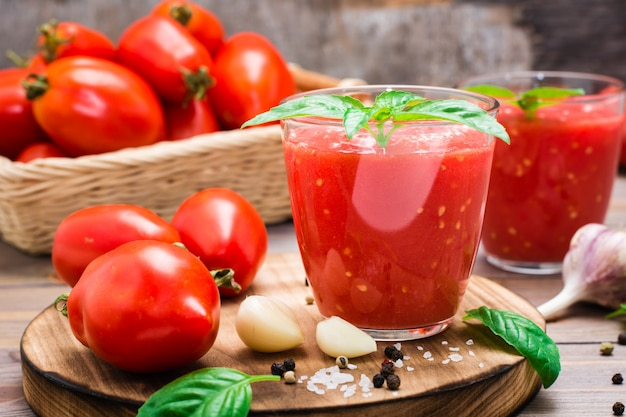 Succo di pomodoro fresco con foglie di basilico in bicchieri e ingredienti per la sua preparazione su un tavolo di legno