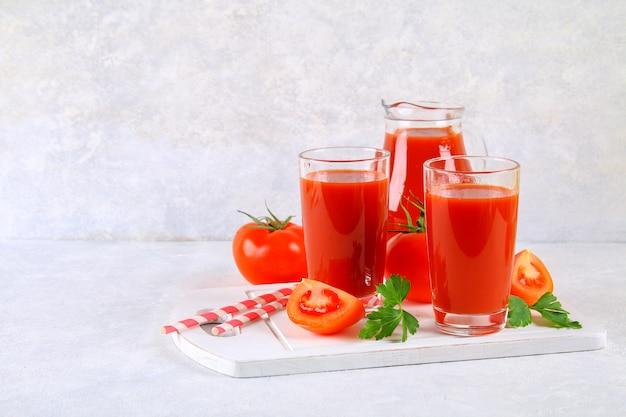 Succo di pomodoro in bicchieri e una brocca su un tavolo di cemento grigio.