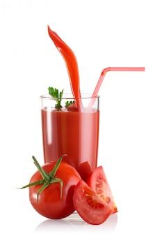 Succo di pomodoro versato nel bicchiere di decanter e pomodoro