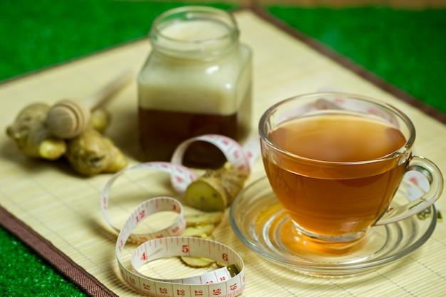 Succo di zenzero in una tazza trasparente e vaso di miele posto accanto con nastro di misurazione