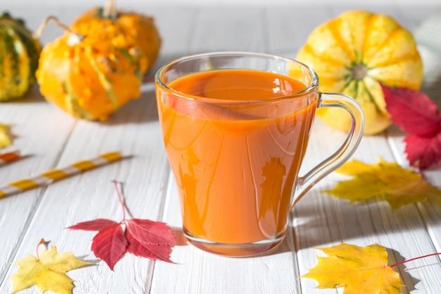 Succo di zucca fresco in tazza di vetro, zucche e foglie di acero cadute. concetto di bevanda caduta