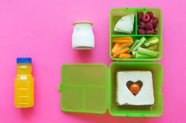 Succo e yogurt vicino al lunchbox con il cibo