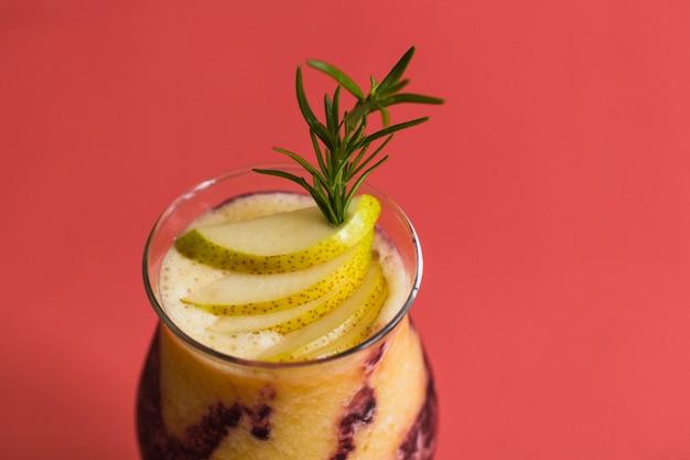 Succo fresco con pera a fette su sfondo rosso