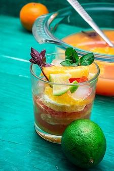 Succo fresco da arance, kiwi e pompelmo su fondo in legno turchese.