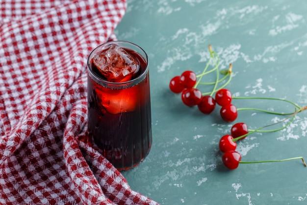 Succo ghiacciato in una brocca con la vista dell'angolo alto delle ciliege sull'asciugamano di cucina e del gesso