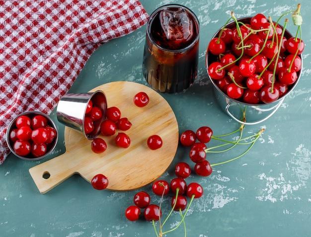 Succo in una brocca con ciliegie, tagliere piatto disteso su intonaco e canovaccio