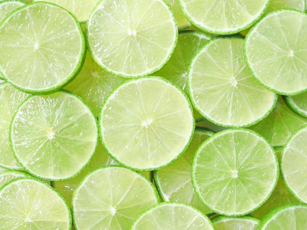 Succose fette di limone, verde lime e verdure fresche e frutta.