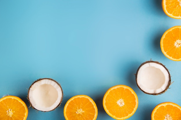 Succose metà arancione e metà cocco bianco su uno sfondo luminoso, blu estate