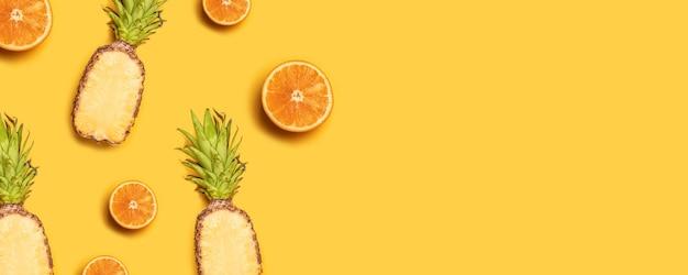Succosi frutti tropicali su uno sfondo giallo: arance, noci di cocco, limoni, ananas.