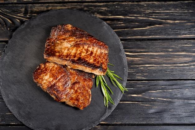 Succoso pezzo di carne fritta si trova su un piatto di pietra contro un tavolo di legno nero