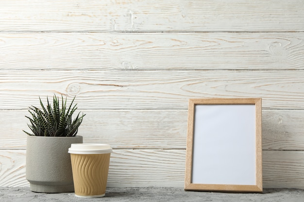 Succulente, caffè e cornice su sfondo bianco in legno, spazio per il testo