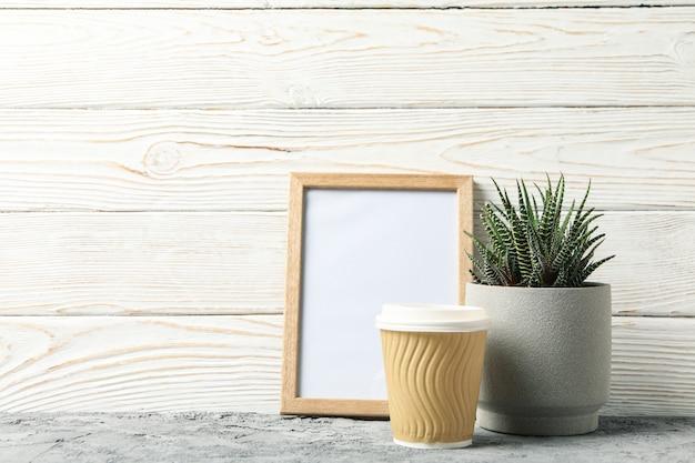 Succulente, caffè e cornice su superficie di legno bianco