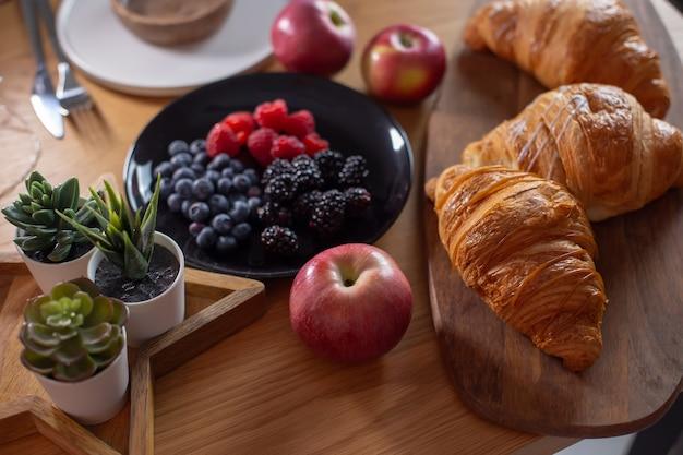Succulente, cornetti, frutti di bosco, mele rosse su un tavolo di legno
