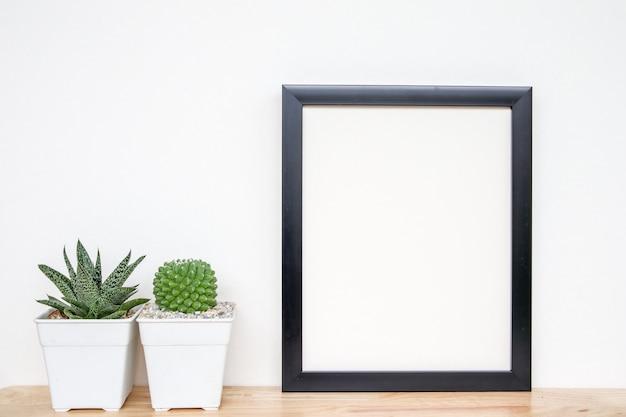 Succulente o cactus in vasi di cemento su sfondo bianco sullo scaffale e mock up cornice foto