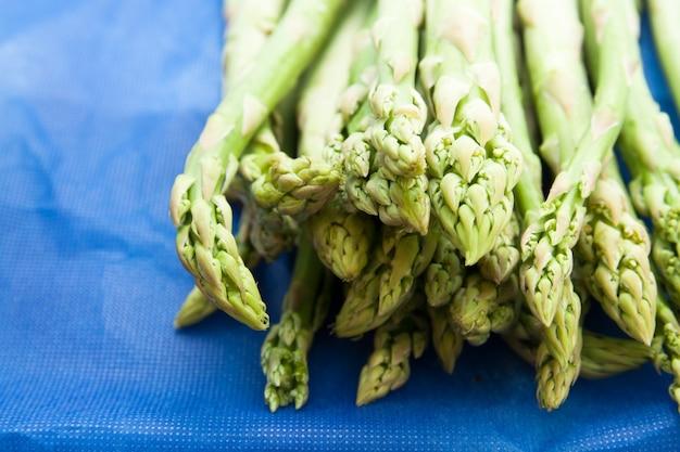 Suggerimenti verdi di asparagi freschi su sfondo blu