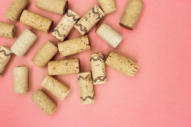 Sugheri assortiti del vino dalla vite bianca e rossa sul fondo di carta rosa con spazio vuoto per il vostro testo. vista dall'alto e disteso.