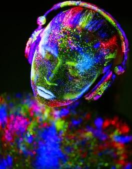 Sul corpo di una ragazza dipinto dj deck. ragazza seminuda dipinta nei colori uv.