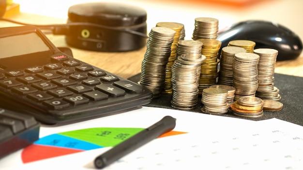 Sul mucchio di monete da scrivania, calcolatrice, tastiera, budget finanziario, grafici e carta per appunti