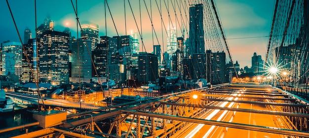 Sul ponte di brooklyn di notte con il traffico automobilistico, new york.