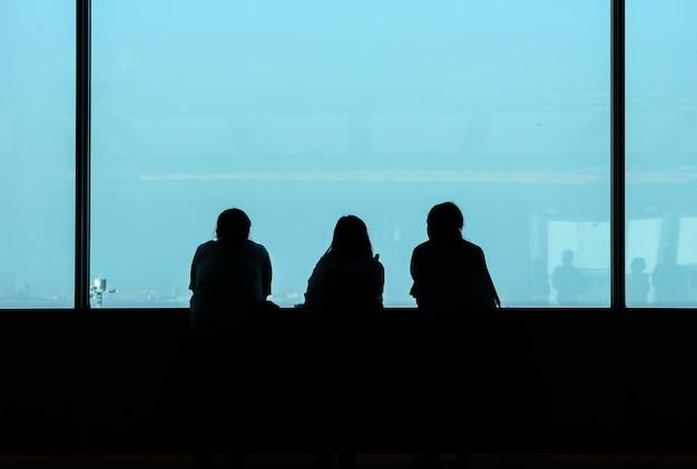 Sul retro di tre donne che guardano la città dall'alta finestra dell'edificio.
