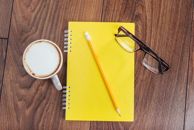 Sul taccuino di legno matita, caffè e fiori.