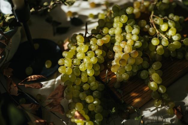 Sul tavolo al sole del mattino giace un grappolo di uva verde