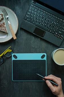 Sul tavolo c'è un laptop, una tavoletta grafica e una tazza di caffè.