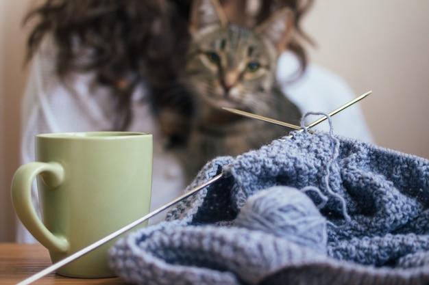 Sul tavolo c'è un lavoro a maglia e una tazza, una ragazza e un gatto