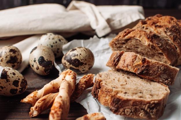 Sul tavolo giacciono uova di quaglia di pane saraceno scuro e grissini italiani.