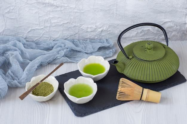 Sul tavolo il tè matcha in ciotole, la frusta, il cucchiaio, la teiera