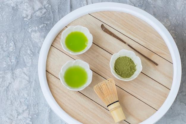 Sul tavolo il tè matcha in ciotole, una frusta da tè e un cucchiaio