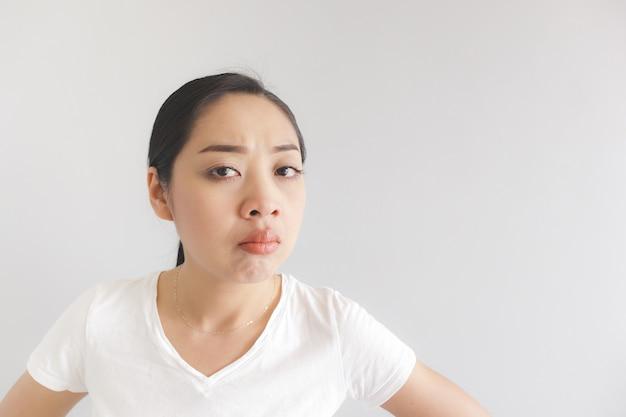 Sulk e scontroso espressione faccia di donna in t-shirt bianca. concetto di offeso stizzoso e imbronciato.