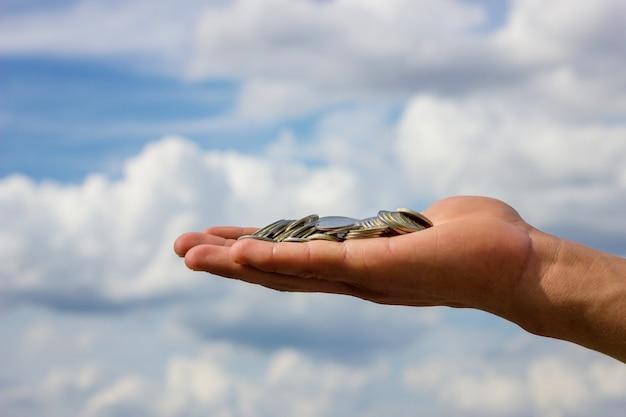 Sulla mano le monete sullo sfondo del cielo
