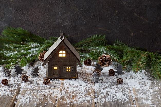 Sulla tavola di legno rami di abete rosso, coni e una casa in legno - sfondo di natale