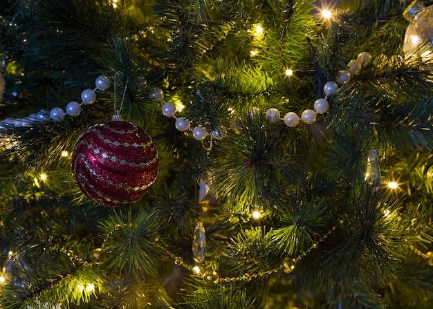 Sulle luci dell'albero di natale e una palla rossa