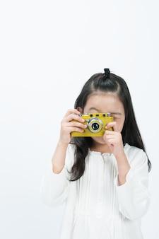 Sullo sfondo bianco, un bambino sta filmando la parte anteriore con una macchina fotografica.
