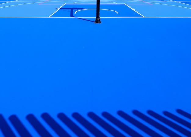 Sullo sfondo del pavimento di un intenso campo sportivo blu con linee bianche.