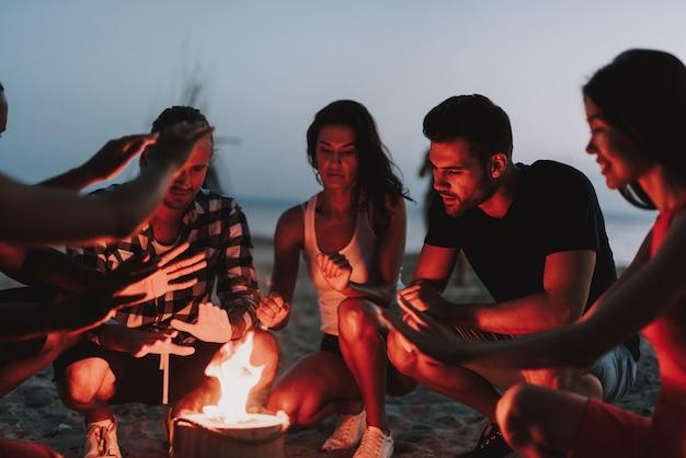 Summer company warming hands around burning log.