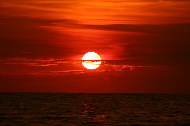 Sun indietro sull'onda di orizzonte del cielo al tramonto sul mare di superficie