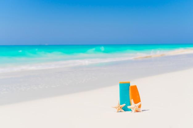 Suncream bottiglie, bicchieri, stelle marine sulla spiaggia di sabbia bianca