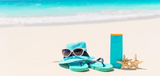 Suncream bottiglie, occhiali da sole, infradito stelle marine su fondo bianco sabbia oceano