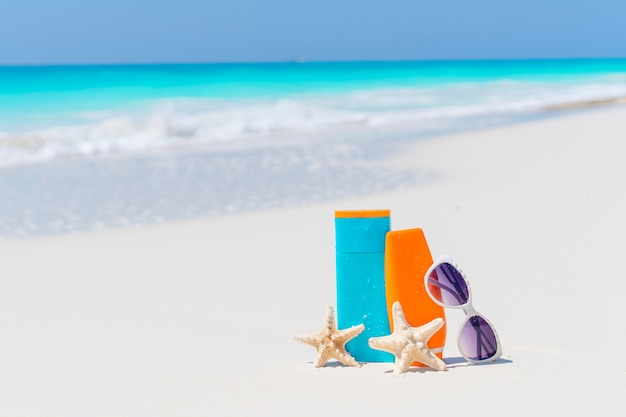 Suncream bottiglie, occhiali da sole, stelle marine su fondo bianco sabbia oceano