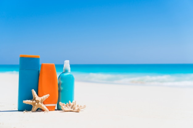 Suncream bottiglie, occhiali, stelle marine sulla spiaggia di sabbia bianca con vista sull'oceano